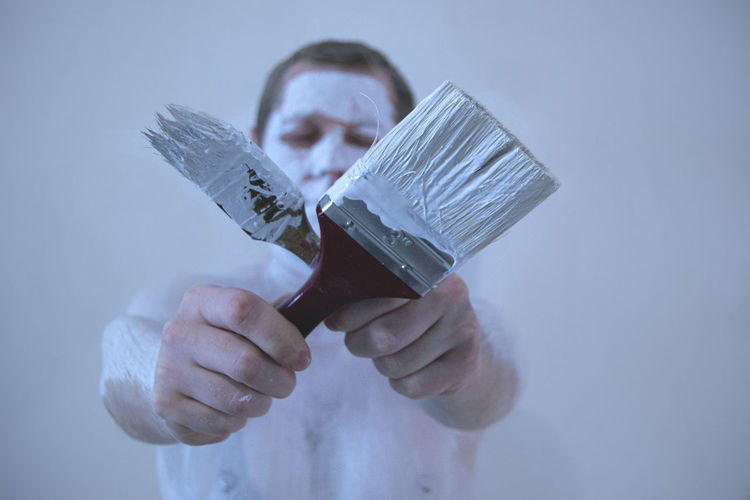 Man with body paint holding paint brush against white background