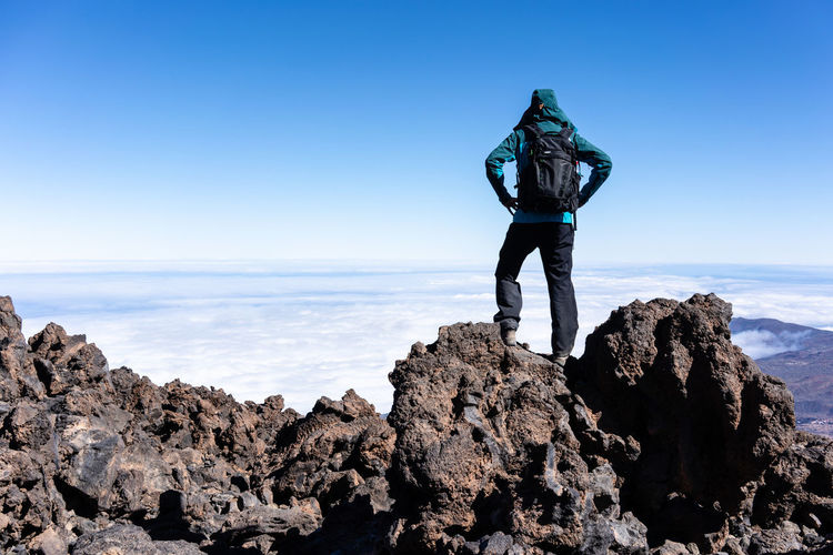 Full Length Of Man Wearing Warm Clothing Standing On Cliff Against Sky