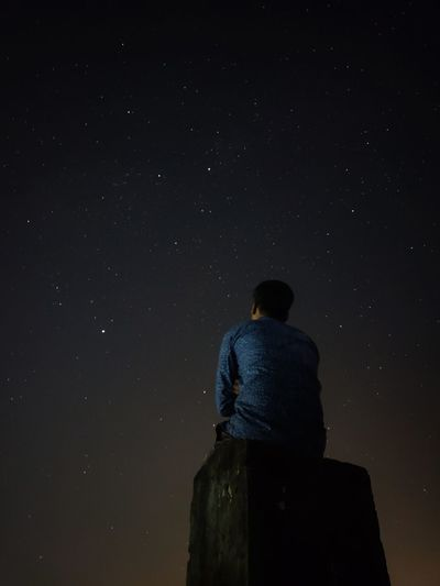 Low angle view of man sitting on rock against star field at night