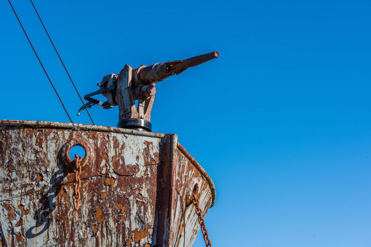Low angle view of abandoned ship against clear blue sky