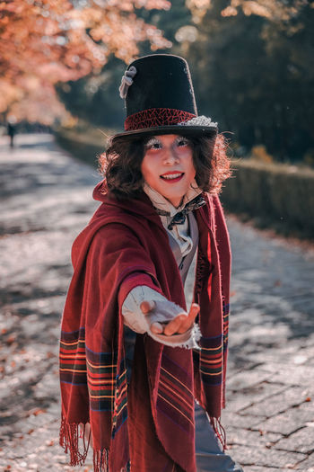 Portrait of smiling young woman cosplaying mad hatter in top hat during winter