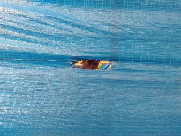 Man looking through torn blue tarpaulin