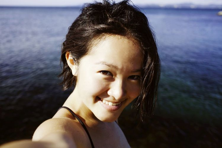 Portrait Of A Smiling Young Woman Against Calm Sea