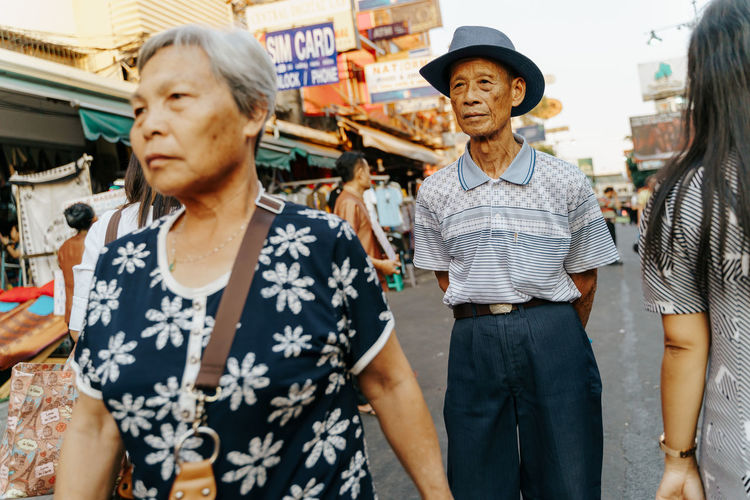elderly people in Bangkok, Thailand Adult Women City Lifestyles People Real People Market Leisure Activity Casual Clothing Hat Retail  Standing Men Architecture Group Of People Senior Adult Focus On Foreground Day Clothing Incidental People Consumerism The Art Of Street Photography