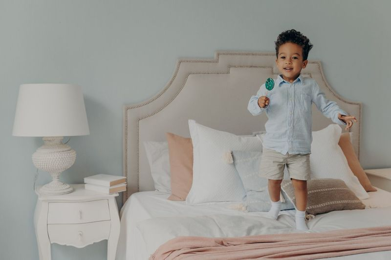 Boy holding lollipop while standing on bed at home
