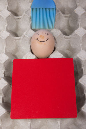 Cartoon face expression at egg and red board with finger also plastic brush Angry; Anthropomorphic Smiley Face Blue Brush; Blue Plastic Brush; Brush; Close-up Confuse; Egg Excited; Expression; Freshness Indoors  Joke; No People Plastic; Sad; Scare; Shy; Sick