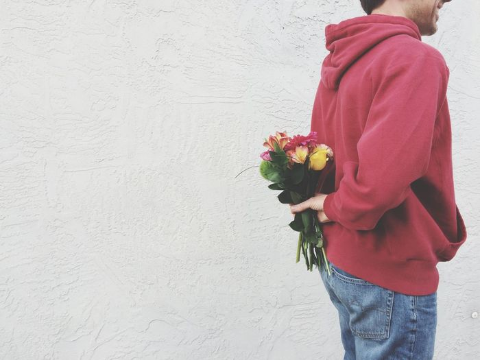 Midsection of man hiding flower bouquet back against wall