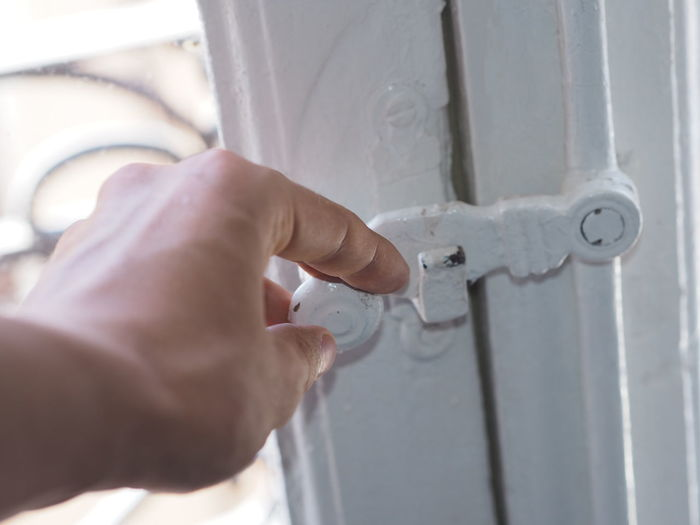 Cropped Hand Of Man Holding Latch On Door