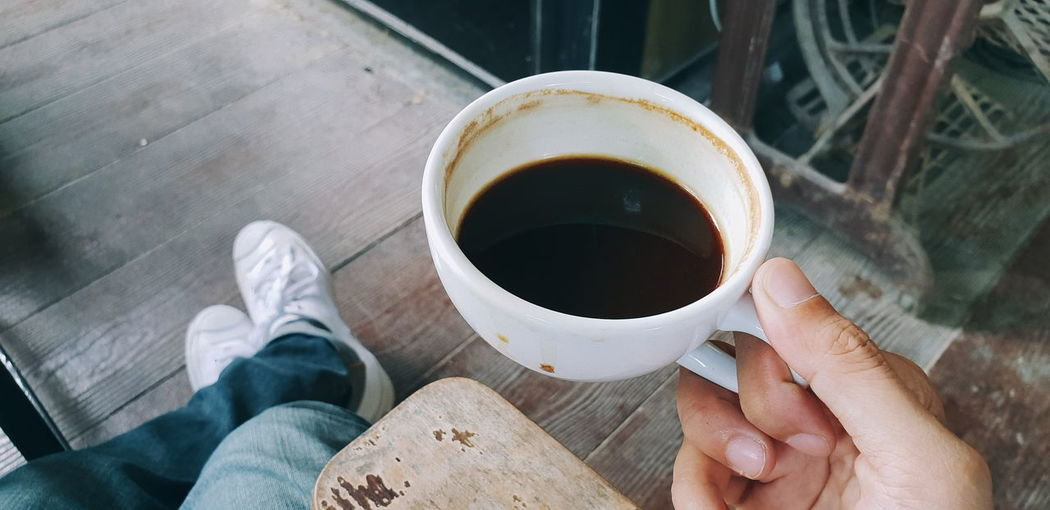 Low section of person holding coffee cup