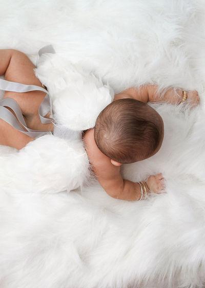 Cute baby in costume lying down on rug