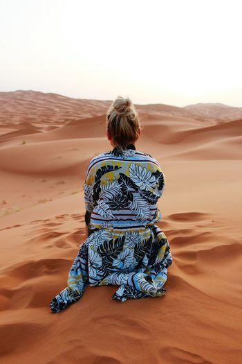 Rear view of woman sitting on sand dune