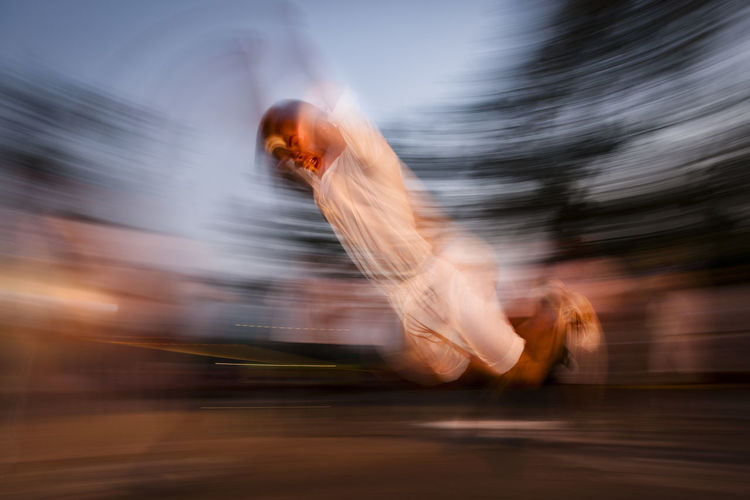 Blurred motion of man jumping at public park during sunset