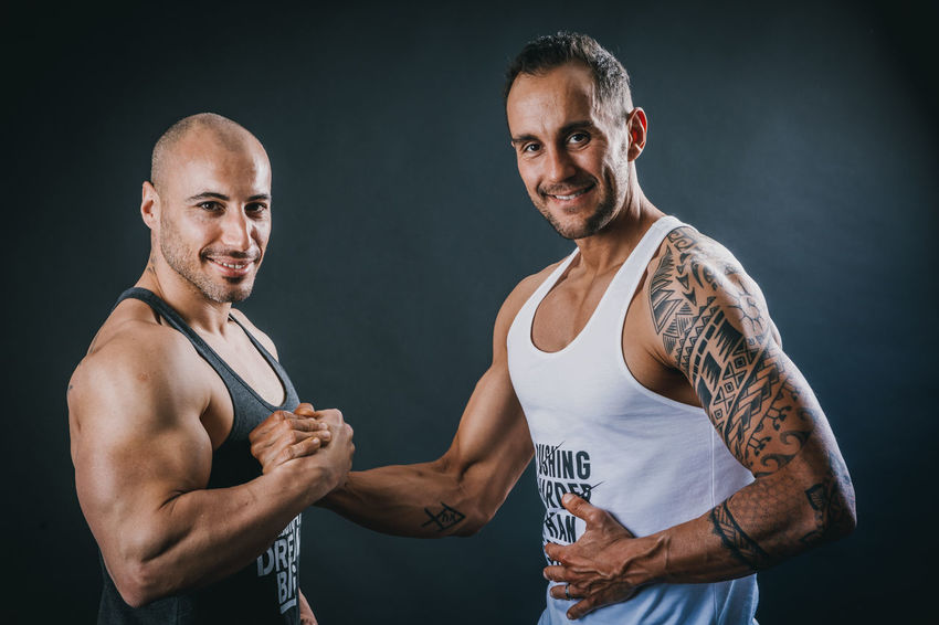 Let me become your food coach This Is Strength Two People Men Indoors  Tattoo Looking At Camera Portrait Adult Standing Mid Adult Men Muscular Build Young Men People Real People Lifestyles Front View Males  Young Adult Mid Adult Confidence  Tank Top Black Background Confidant Teamwork Team Sport