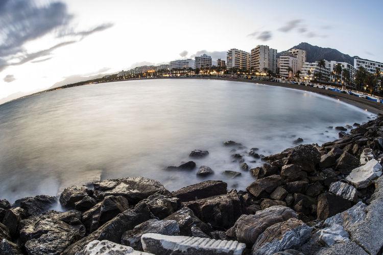 Sea by rocks in city against sky