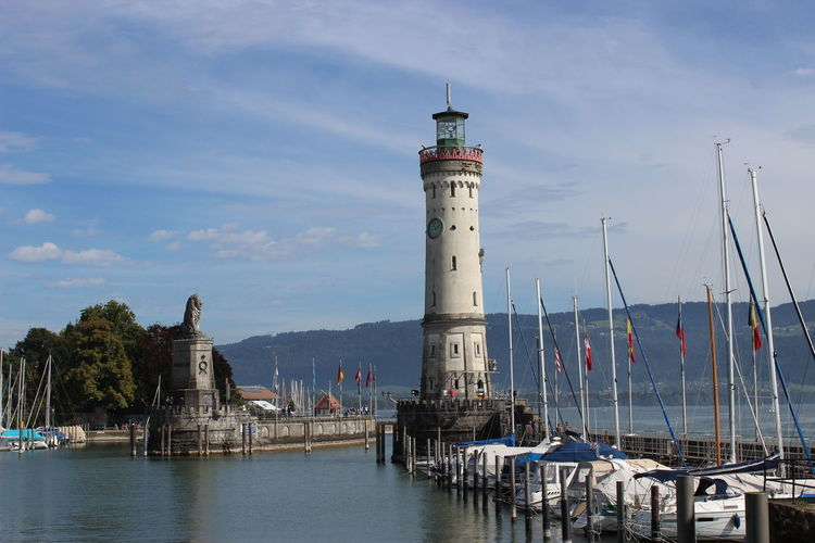 Lindau lighthouse by harbor against sky