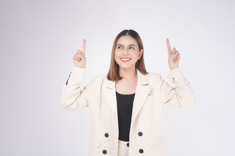 Portrait of smiling young woman standing against white background
