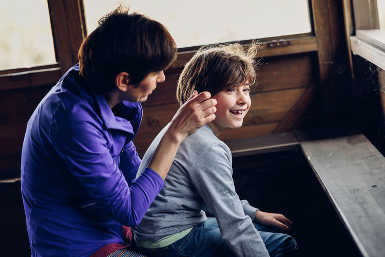 Mother with her seven year old daughter laughing in a cabin in the countryside. Lifestyle concept. Boys Casual Clothing Child Childhood Emotion Family Females Hairstyle Happiness Indoors  Innocence Leisure Activity Lifestyles Males  Men Positive Emotion Real People Sister Smiling Three Quarter Length Togetherness Two People
