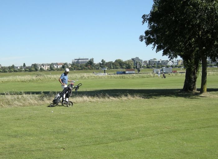 Golfer with rack on grassy field against clear blue sky