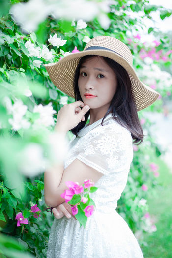 Side View Portrait Of Beautiful Woman Standing By Flowers At Park