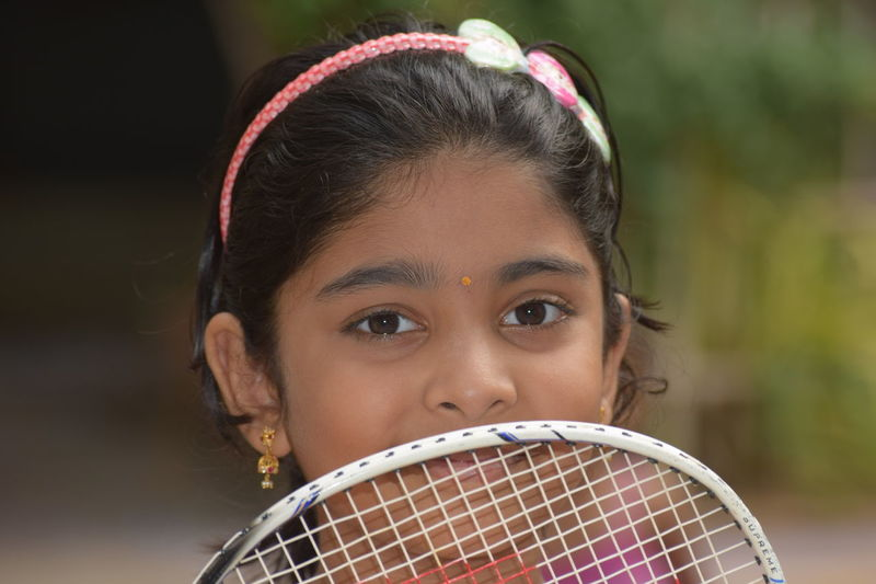 Close-up portrait of girl with badminton racket