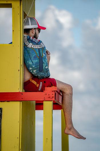 Boy sitting against yellow sky