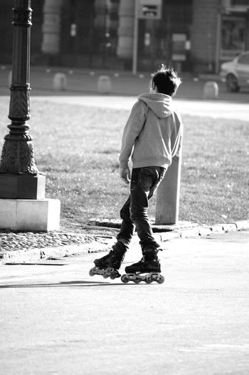 Rear View Of Man Roller Skating On Road