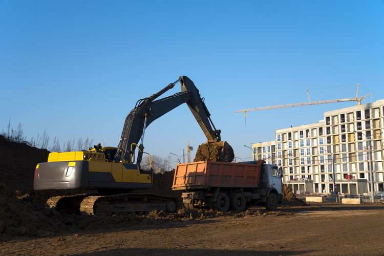 Construction site in city against clear sky