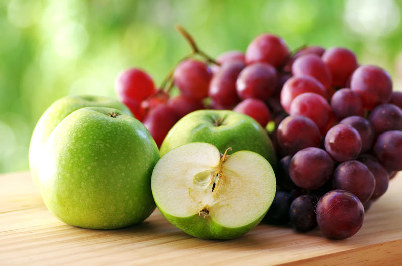Close-up of granny smith apples and red grapes on table