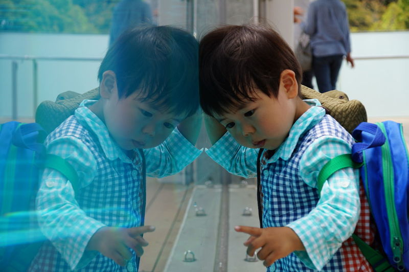 Cute boy in school uniform reflecting on glass wall