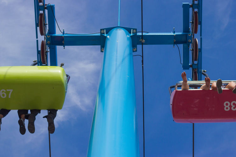 Low Section Of People On Ski Lift Against Blue Sky