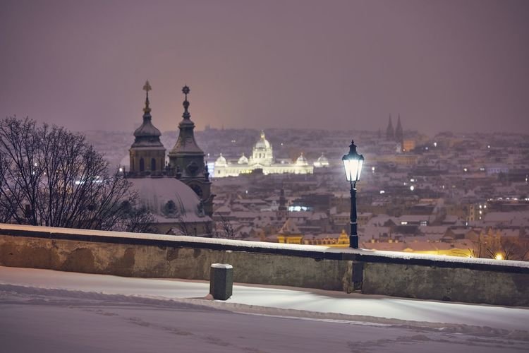 Illuminated buildings in city during winter