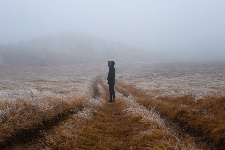 Man standing on landscape during foggy weather