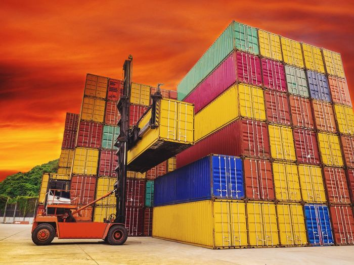 Vehicle stacking colorful cargo containers against orange sky