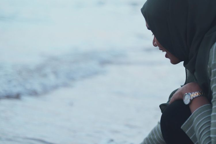 Side view of young woman wearing hijab on shore at beach