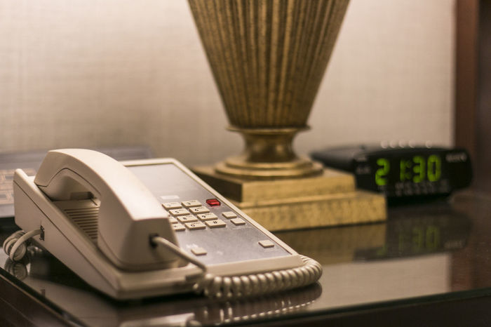 Telephone at hotel room sitting on bedside table along with the table lamp and alarm clock. Alarm Clock Clock Desk Dial Front Desk Front Table Home Hotel Hotel Room Number Old Old Telephone Phone Receptionist Retro Table Table Lamp Technology Telephone