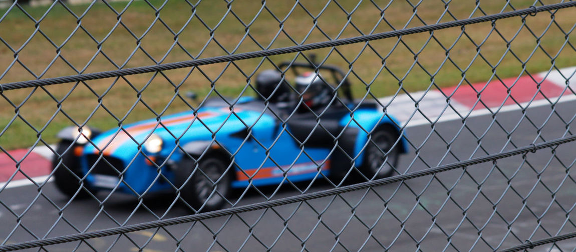 Chainlink Fence Focus On Foreground Multi Colored Outdoors Racecar Racetrack Nürburgring Racetrack Nordschleife Grüne Hölle Caterham7 620R Car Cars Carswithoutlimits