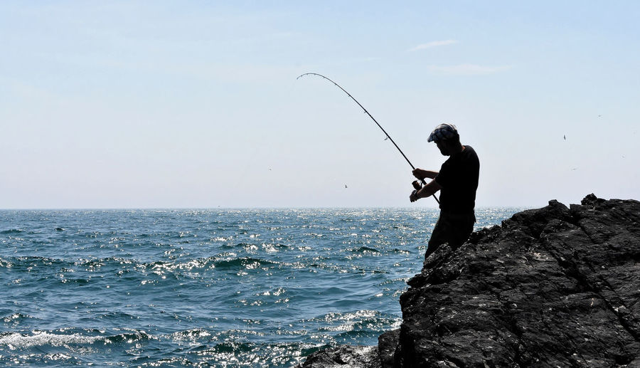 Side view of man fishing in sea against sky