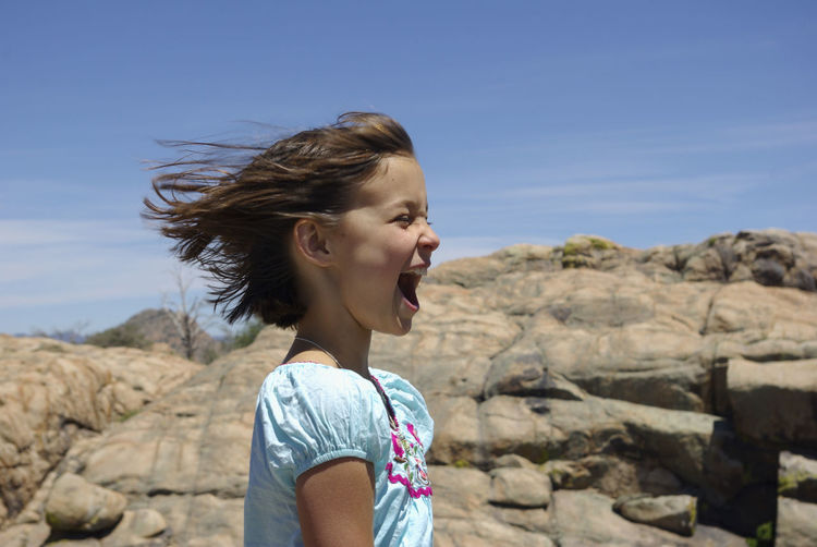 Side view of girl screaming by rock against sky