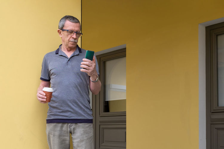 Man wearing sunglasses standing against yellow wall