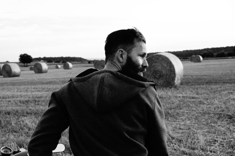 Rear View Of Man Against Hay Bales On Field Against Sky