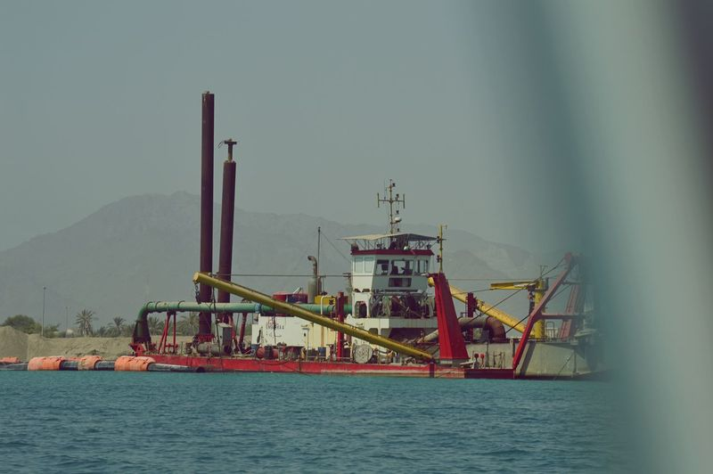 Calm Coast Coastline Commercial Dock Diging Underwate Dredger Dredger Ship Early Morning Faraway Gulf Industry Middle East Mountain Mountain Range Mountains Ocean Oil Industry Sea Sea And Sky Sea Construction Sea Life Sea View Sky Water Waterfront