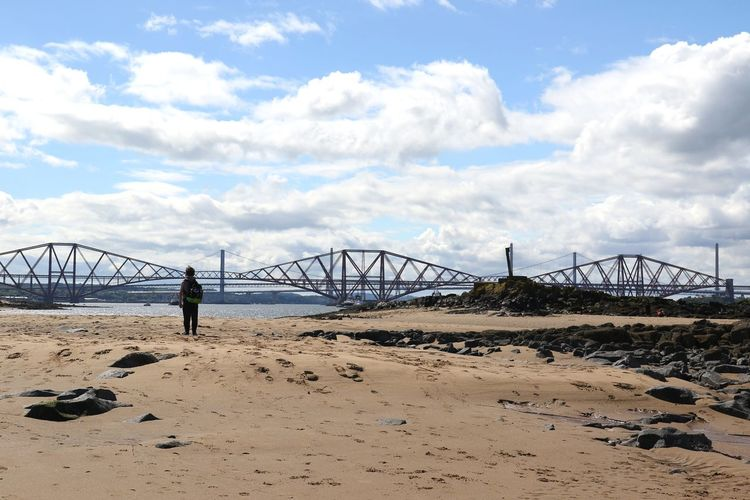 Person Standing At Beach Against Firth Of Forth Rail Bridge