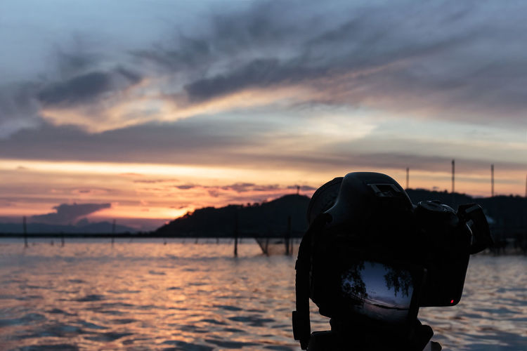 Man photographing sea against sky during sunset