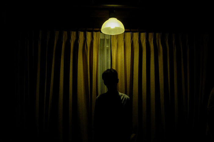 REAR VIEW OF MAN STANDING AGAINST ILLUMINATED LAMP