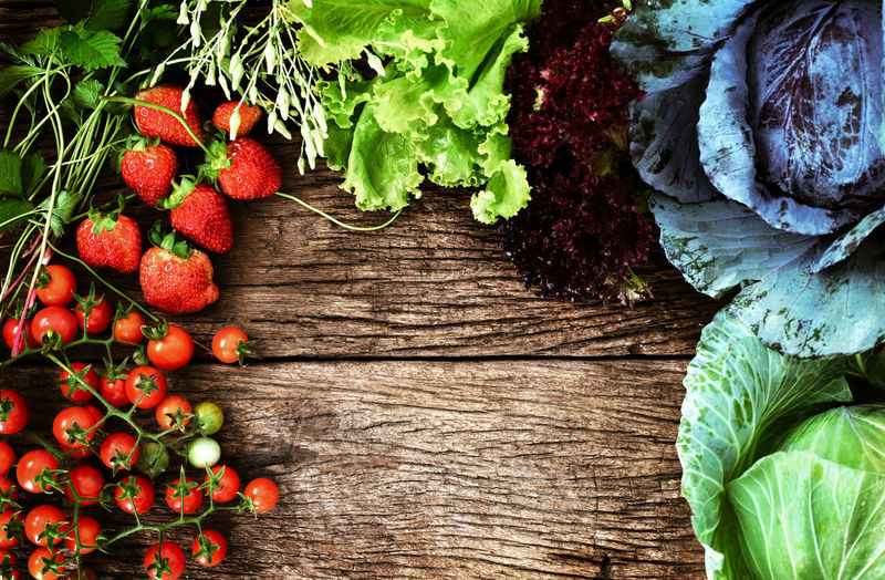 View from above of mix vegetable and fruit on wooden background with space for text, clean eating food Healthy Eating Food And Drink Food Freshness Fruit Directly Above Wood - Material Vegetable Berry Fruit High Angle View Ripe Vegetarian Food Table Freshness Organic Wellbeing Red Green Color Rustic Border Clean Food Clean Eating