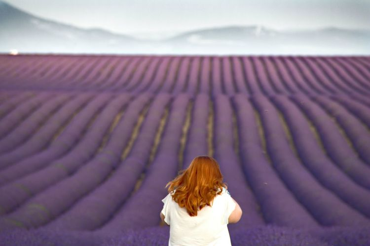 Rear View Of Woman Standing Against Lavender Field Against Sky