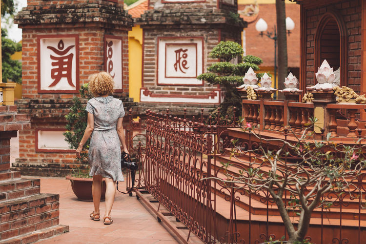 Woman With Camera Walking On Footpath At Temple