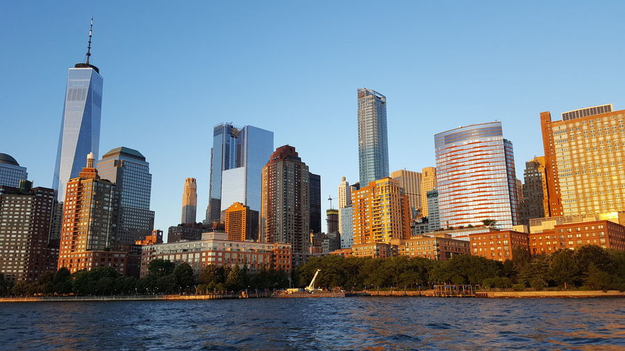 Low angle view of city skyline by river against clear sky