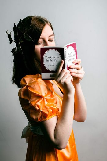 Young woman holding camera over white background