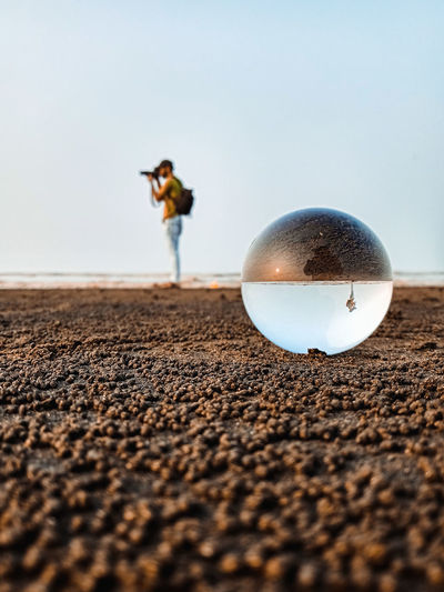 Close-up of crystal ball on sand against clear sky